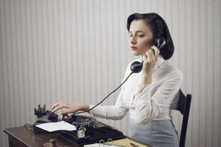 Perfect secretary talking on phone at desk photo