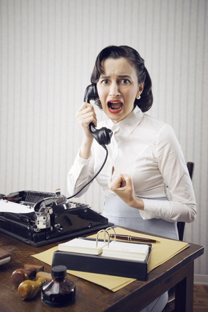 Scared Young Woman shouting into telephone photo