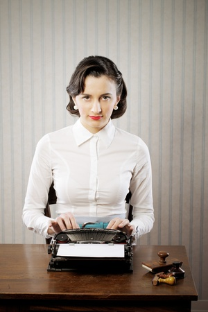 vintage typewriter: Retro business woman typing in her office