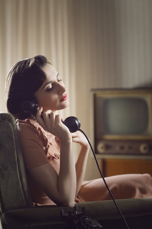 vintage living room: Woman talking on retro phone at home Stock Photo