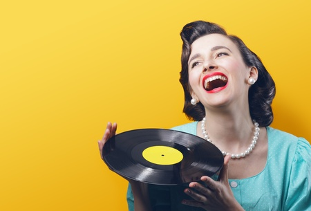 vintage woman: Happy woman with a vinyl record in her hands
