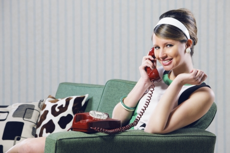 Happy female smiling while talking on a red phone Stock Photo - 19433028
