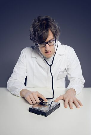 Doctor / Technician wearing a lab coat and stethoscope examining an hard disk Stock Photo - 19433014