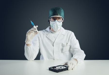 virus informatico: Concepto de virus inform?tico. T?cnico  Doctor con la jeringuilla y el disco duro Foto de archivo