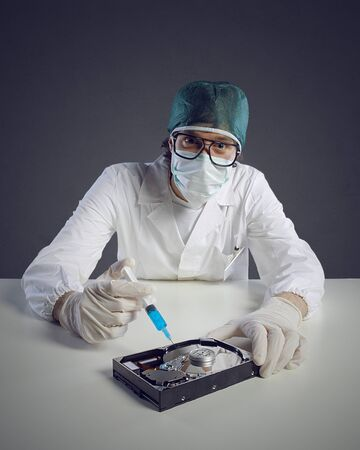 Computer virus concept. Technical / Doctor with syringe and hard disk photo