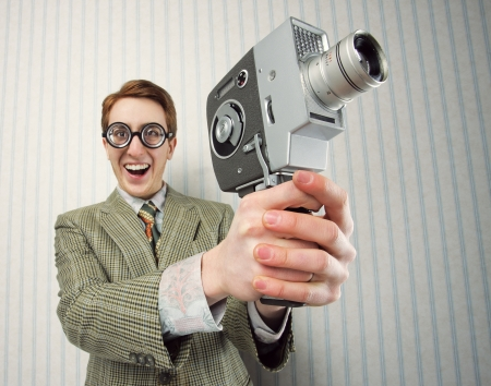 ugliness: Nerdy young man using old fashioned cine camera Stock Photo