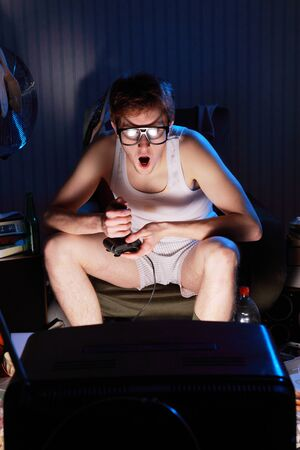 A excited teen plays video console games on His television photo
