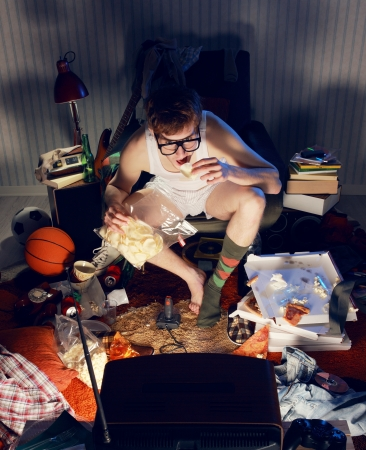 Nerd boy sitting and watching something interesting on TV. He is eating some snacks. Stock Photo - 19433031