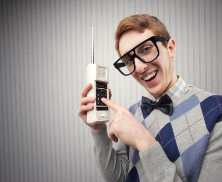 nerd glasses: Nerd student with an old mobile phone  Stock Photo
