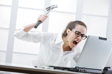 smash: Freaked out businesswoman with a hammer ready to smash her laptop computer