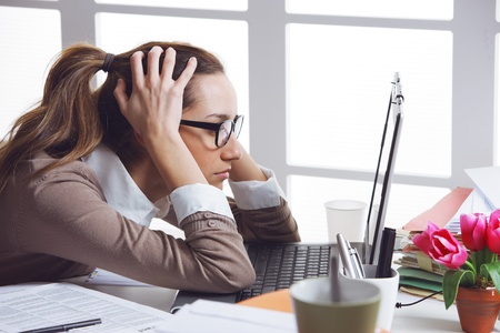 Young and beautiful businesswoman tired from work in the office.Woman holding her head Stock Photo - 19433003