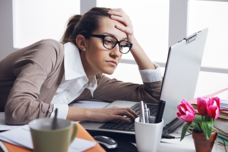 Young and beautiful businesswoman tired from work in the office.Woman holding her head Stock Photo - 19433020