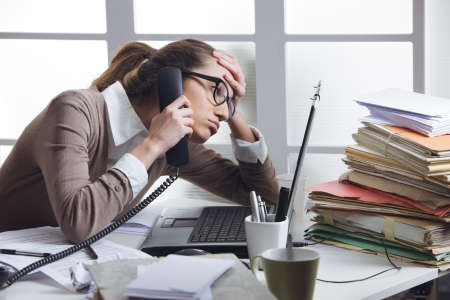 A stressed business woman looks tired  she answer telephones in her office photo