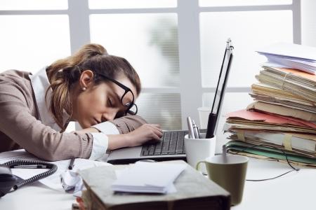 durmiendo: Empresaria cansada que duerme en el escritorio, delante de la pantalla del ordenador.