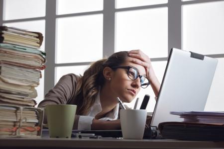 Femme d'affaires Frustated avec le travail, a beaucoup de paperasse au bureau