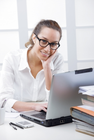 Business woman portrait smiling in an office in front of her laptop Stock Photo - 19433001