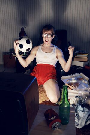 Nerd boy excited by goal scored during sports competition photo