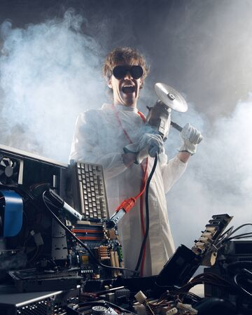destroy: Crazy computer technician is trying to repair a computer Stock Photo
