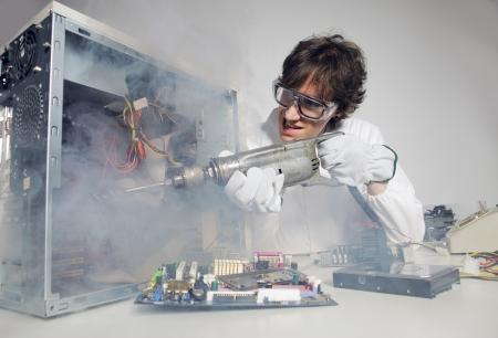 �crazy: Tecnico informatico pazzo sta cercando di riparare un computer con un trapano Archivio Fotografico