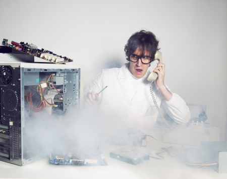 it support: Computer technician in his laboratory is talking on the phone Stock Photo