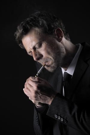 hombre fumando: Maduro hombre de fumar cigarrillos sobre fondo negro Foto de archivo