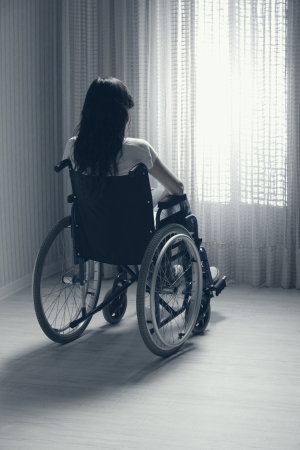 Young woman seated in a wheelchair looking out a window photo