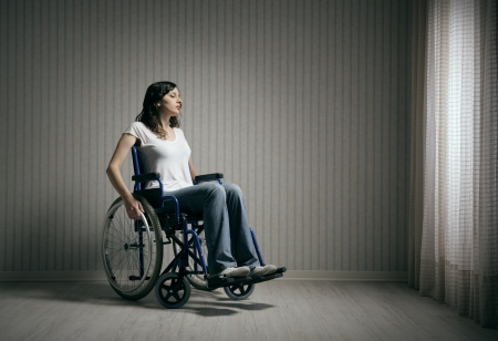 Sad woman sitting on wheelchair in empty room Stock Photo