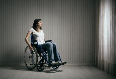 silla de ruedas: Triste mujer sentada en silla de ruedas en la habitación vacía Foto de archivo