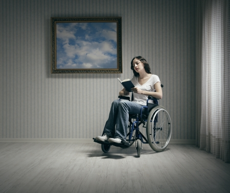 Disabled young woman reading a book  in a wheelchair photo