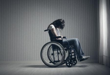 persona en silla de ruedas: Triste mujer sentada en silla de ruedas en la habitaci?n vac?a
