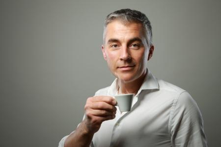 man drinking coffee: Handsome mature man enjoying a hot drink
