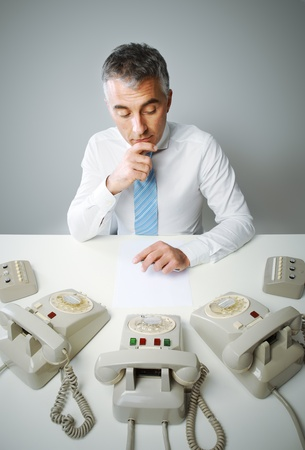 Mature business man with three phone waiting for a call photo