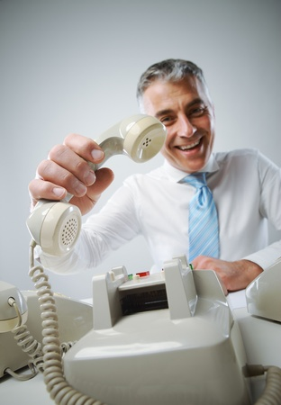 Portrait of a smiling mature business man with phone, focus on hand photo