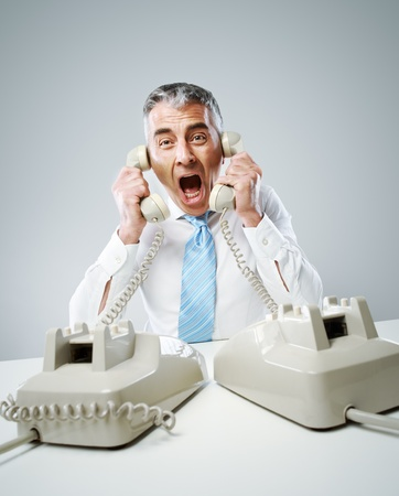 answering call: A stressed businessman shouts into the two handsets that he is holding.