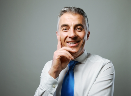 Portrait of a handsome mature man smiling on grey background photo