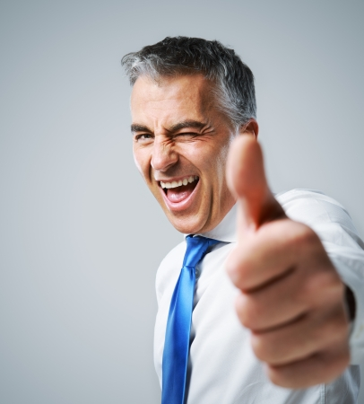 thumbs up man: Happy mature business man showing thumbs up sign