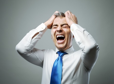 Frustrated mature businessman with his hands on his head while yelling photo