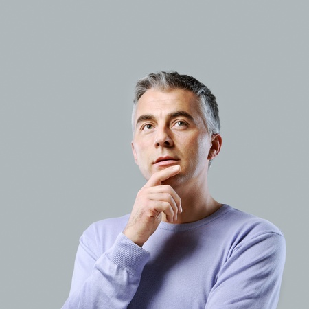 Portrait of casual man thinking and looking up photo