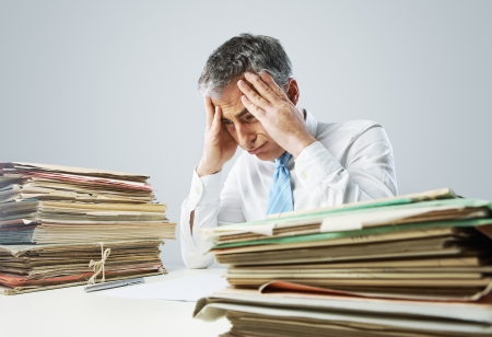emotional stress: Stressed businessman, with a too much paperwork and files piled up on the table Stock Photo