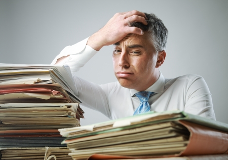 too much: Stressed businessman, with a too much paperwork and files piled up on the table Stock Photo