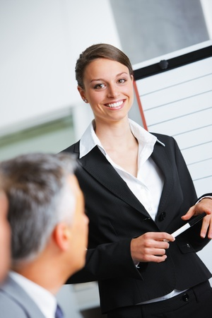 Portrait of a smiling businesswoman giving a presentation at work photo