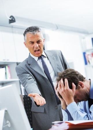 Mature manager shouting at his office worker photo