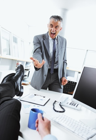 Business man relaxing at desk while his boss shouting angry photo