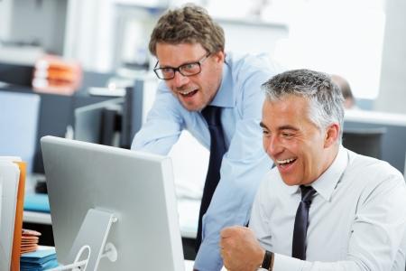 Business team de réussite dans un bureau devant un écran d'ordinateur