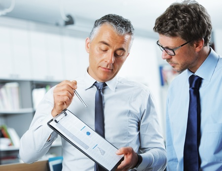 mature business man: Business men discussing together in an office Stock Photo