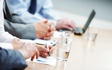 sala de reuniões: Feche acima das mãos de pessoas de negócios durante uma reunião