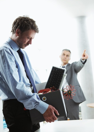 Boss dismissing an employee. Dejected fired office worker carrying a box full of belongings. Stock Photo - 19844648