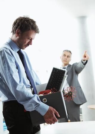 Boss dismissing an employee. Dejected fired office worker carrying a box full of belongings.