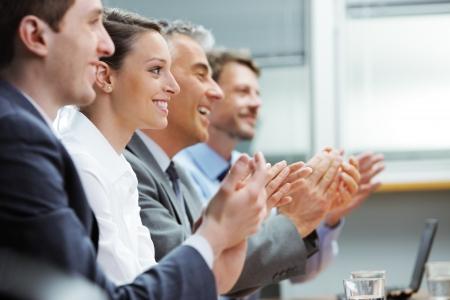 conferentie: Groep vrolijke ondernemers zitten in een rij op een presentatie en klappen