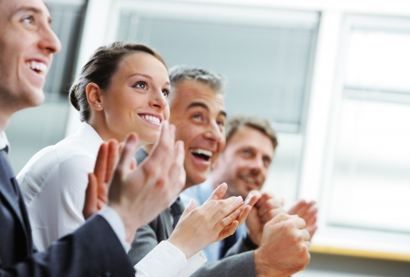 applauding: Group of cheerful businesspeople sitting in a row on a presentation and clapping Stock Photo